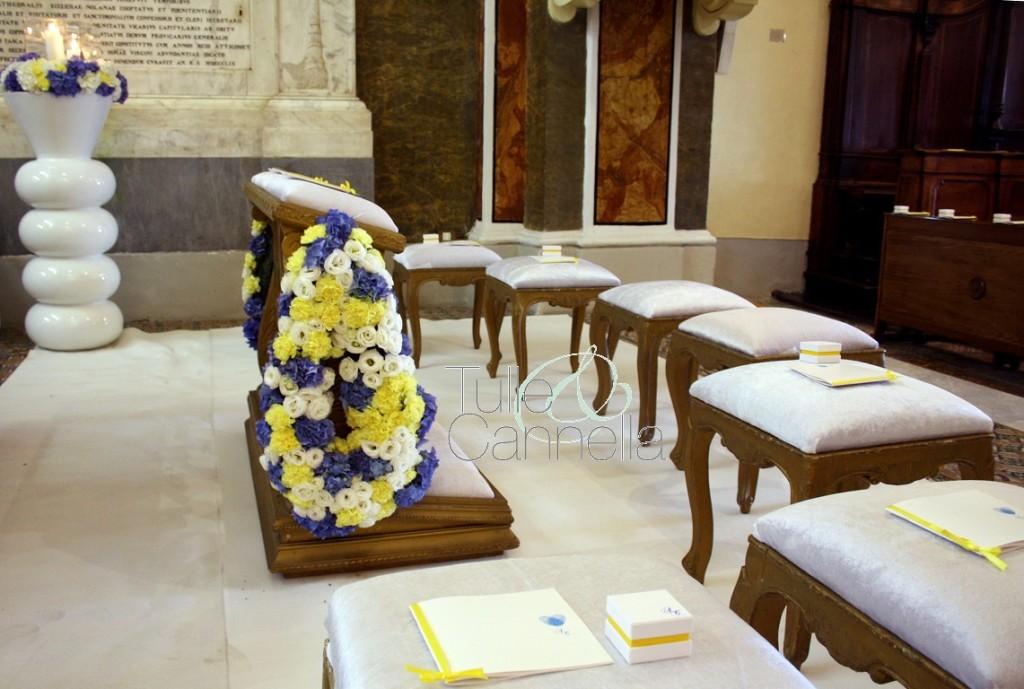 Grandi gocce di fiori bianchi, blu e gialli, adornano l'inginocchiatoio degli sposi
