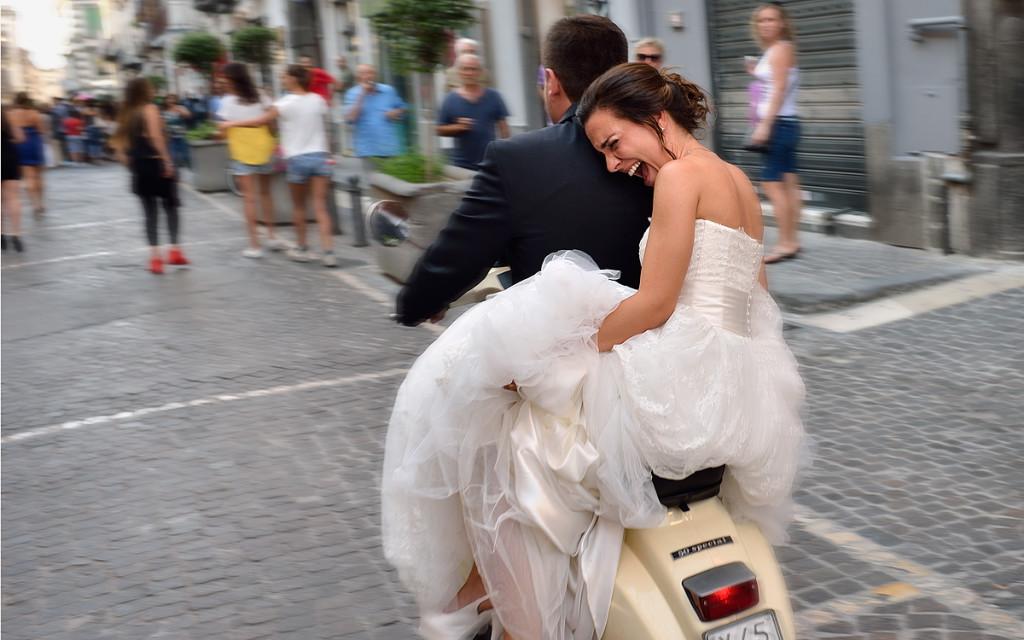 Sposa felice e per nulla preoccupata dai volumi dell'abito, sfreccia abbracciata allo sposo su una vespa vintage - facebook.com/EliaVaccaroFotografo/