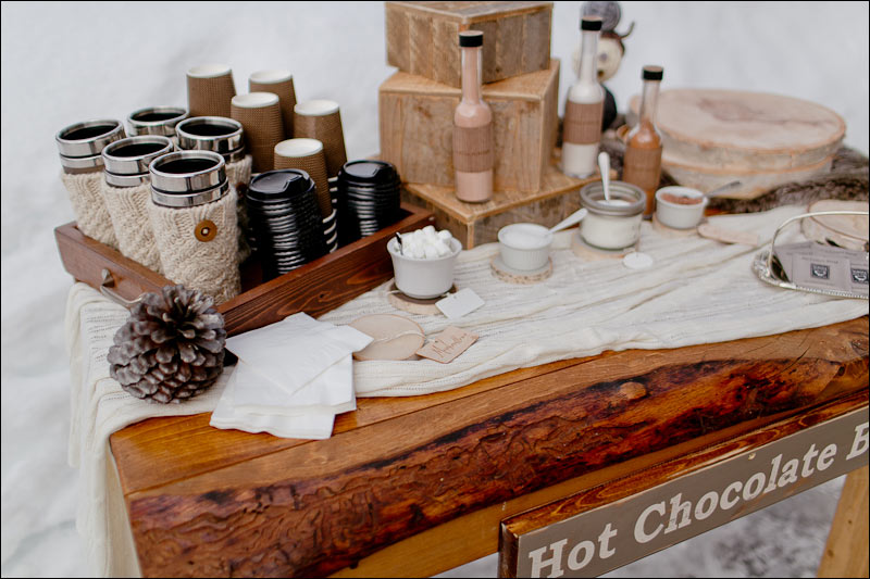 Angolo con Cioccolata calda allestito direttamente sulla neve. Notare le simpatiche maniche di lana per le tazze termiche - juliewilliamsphotography.ca